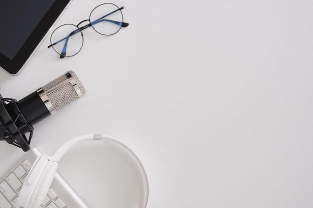 Microfono podcast vista dall'alto, tastiera, tablet e occhiali su sfondo bianco con spazio di copia
