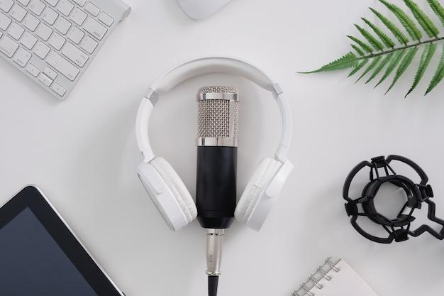 Microfono podcast vista dall'alto, tastiera, tablet e cuffie su sfondo bianco
