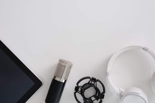 Microfono podcast vista dall'alto, tastiera e tablet su sfondo bianco con spazio di copia