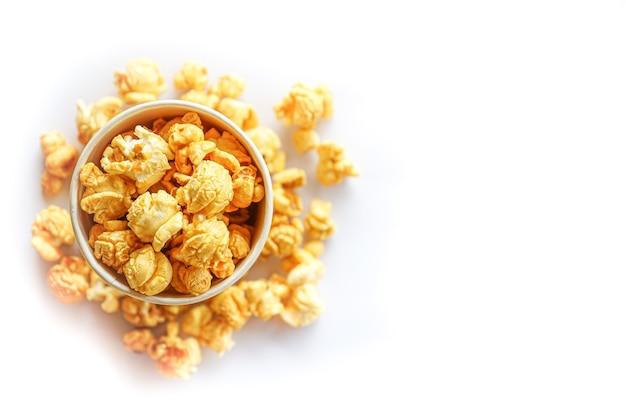 Vista dall'alto di popcorn in vetro di carta su sfondo bianco con spazio di copia