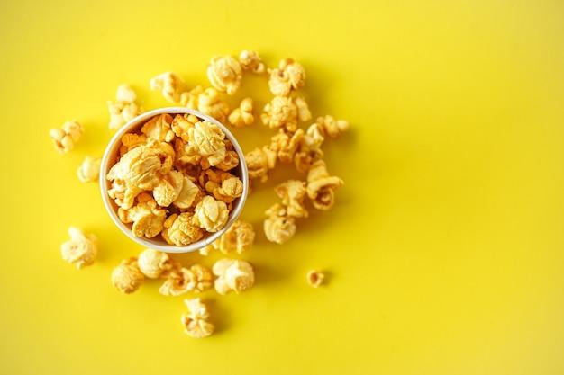 Vista dall'alto di popcorn in vetro di carta su sfondo giallo con spazio di copia