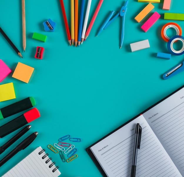 Ritratto di vista dall'alto di un gruppo di strumenti ufficio colorati su sfondo blu pastello