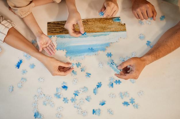 Vista dall'alto al ritratto della famiglia moderna risolvendo puzzle insieme mentre vi godete il tempo al chiuso a casa