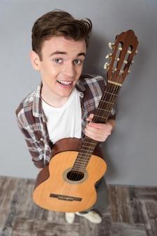 Ritratto vista dall'alto di un giovane in piedi con la chitarra e guardando