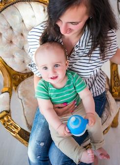 Vista dall'alto di una giovane madre positiva che tiene il suo piccolo figlio tra le braccia mentre è seduto su una bella sedia accogliente nel soggiorno. il concetto di genitori premurosi