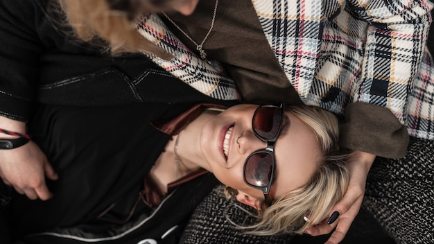 Vista dall'alto su una giovane donna piuttosto positiva con un sorriso affascinante in occhiali da sole alla moda in giacca nera alla moda