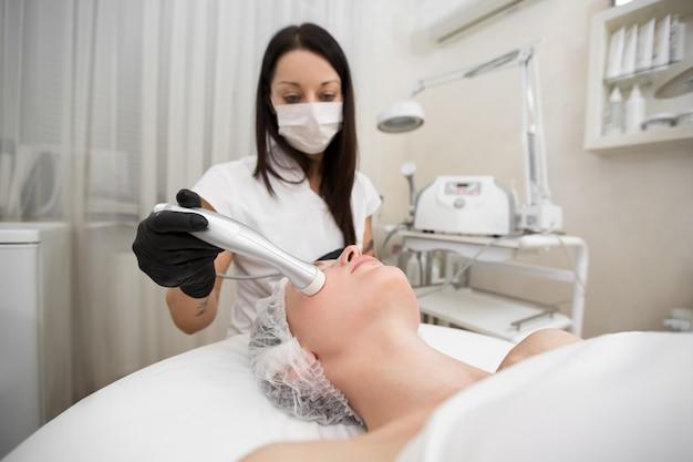 Vista dall'alto della procedura di mesoterapia senza iniezione per una giovane ragazza nel salone della stazione termale.
