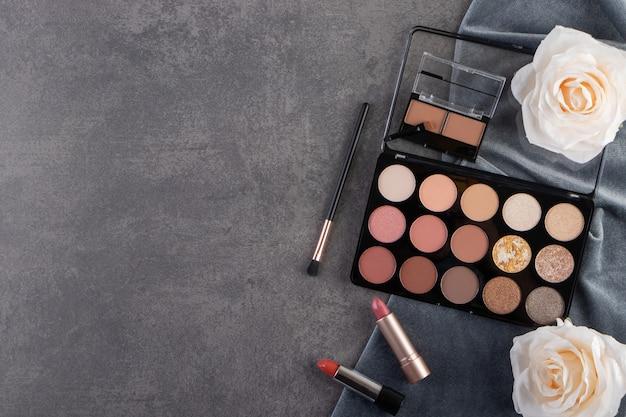 Vista dall'alto del prodotto cosmetico professionale sulla superficie grigia con fiori