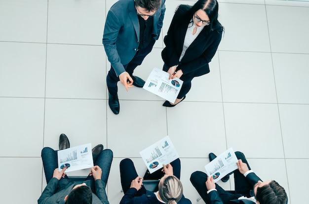 Vista dall'alto. project manager che pone domande in una riunione con il gruppo di lavoro. concetto di affari.