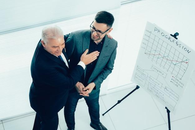 Vista dall'alto. project manager si congratula con il dipendente per una presentazione di successo
