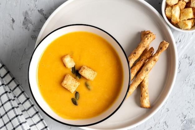 Vista dall'alto di zucca, zuppa di crema di carote in una ciotola. con crostini di pane, semi di zucca e grissini.