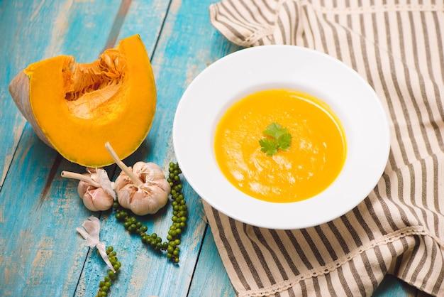 Vista dall'alto della zuppa di zucca e carote con panna e prezzemolo su fondo di legno blu.