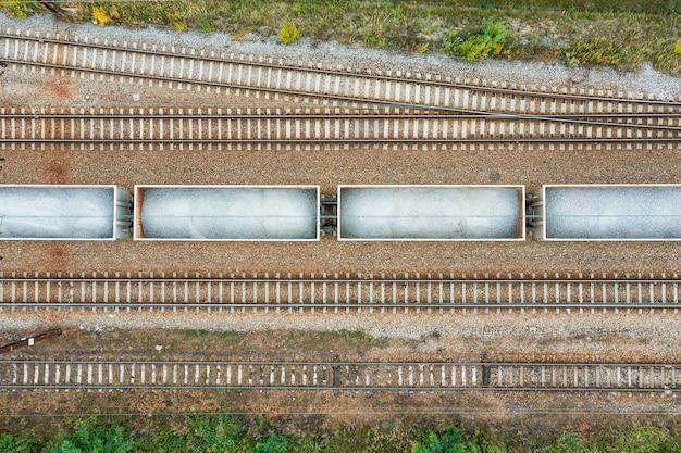 Vista dall'alto dei binari ferroviari con carri con pietra il giorno d'estate
