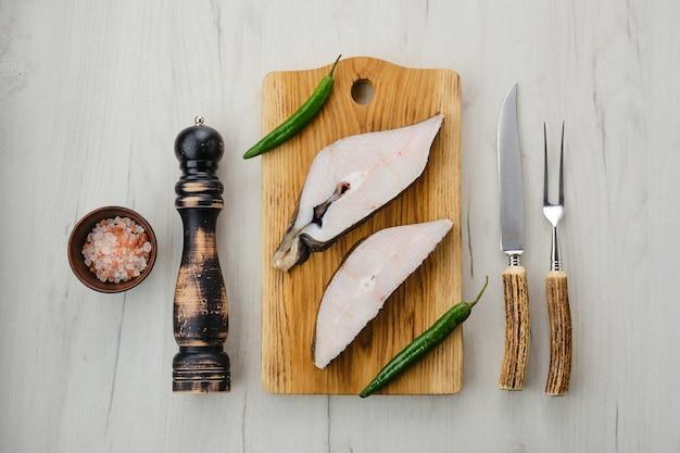 Vista dall'alto di bistecca di halibut fresca cruda sul tagliere di legno con spezie