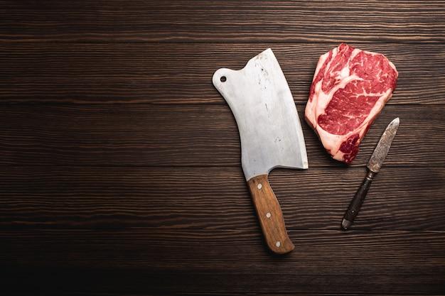 Vista dall'alto della bistecca di carne marmorizzata fresca cruda ribeye con mannaia rustica su fondo di legno con spazio per il testo. cucinare una succosa bistecca organica o un concetto di macelleria, mangiare sano e pulito, primo piano