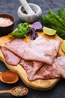 Vista dall'alto di calamari non pelati freschi crudi sul tagliere di legno con spezie ed erbe aromatiche
