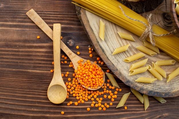 Vista dall'alto pasta cruda con lenticchie arancioni su superficie marrone