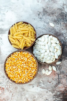 Vista dall'alto calli gialli crudi con semi e pasta all'interno di piatti su superficie chiara