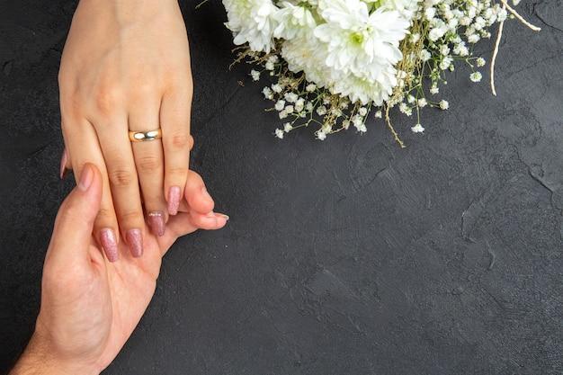 Vista dall'alto che raggiunge le mani mano maschile che tiene la mano femminile con fiori di anello di fidanzamento su sfondo scuro spazio libero