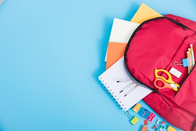 Vista dall'alto zaino rosso della borsa per i bambini di istruzione sull'azzurro