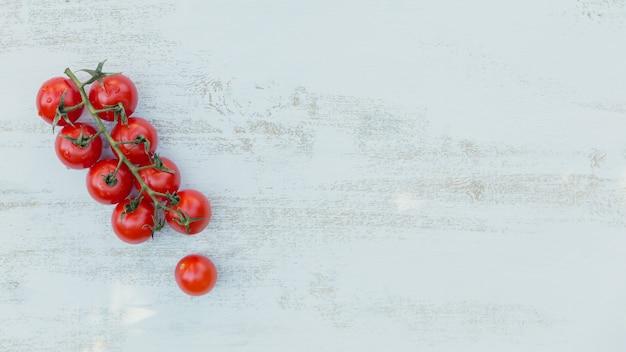 Vista dall'alto di pomodorini rossi su fondo azzurro