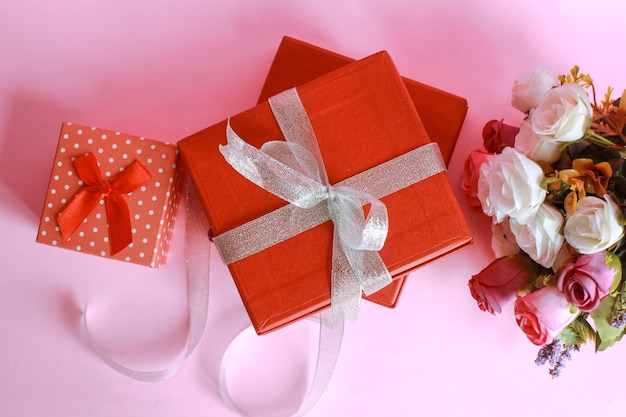 Vista dall'alto della confezione regalo rossa con rose colorate isolato su sfondo rosa