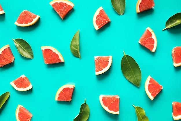 Vista dall'alto di organge rosso frutta e foglie su blu, piatto laici
