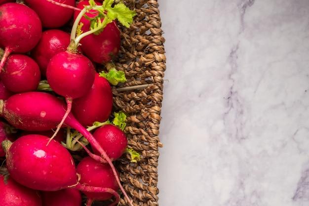 Vista dall'alto di ravanelli rossi maturi in un cesto con grunge, vista dall'alto