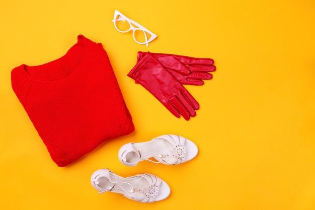 Vista dall'alto di swether rosso, scarpe eleganti, guanti rossi e occhiali bianchi. concetto di moda e design, shopping