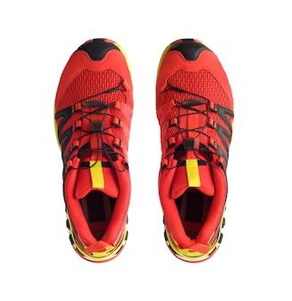 Vista dall'alto di scarpe da trail running rosse o scarponi da trekking isolati su sfondo bianco