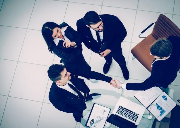 Vista dall'alto: partner commerciali affidabili della stretta di mano dopo la discussione del contratto finanziario in ufficio. la foto ha uno spazio vuoto per il testo.
