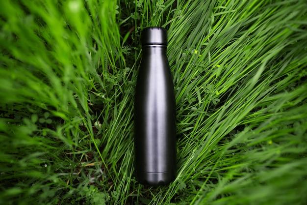 Vista dall'alto del thermos riutilizzabile in acciaio nero per acqua nell'erba verde. zero sprechi. concetto di ambiente. niente plastica.