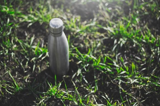 Vista dall'alto della bottiglia d'acqua termica in acciaio riutilizzabile sull'erba.