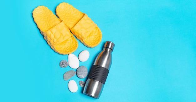 Vista dall'alto della bottiglia d'acqua termica in acciaio riutilizzabile vicino a pantofole gialle e sfondo di pietre.