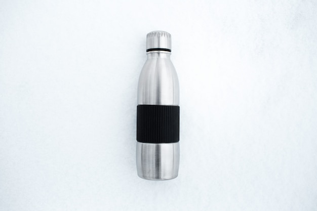 Vista dall'alto della bottiglia d'acqua termica in acciaio riutilizzabile sulla neve.