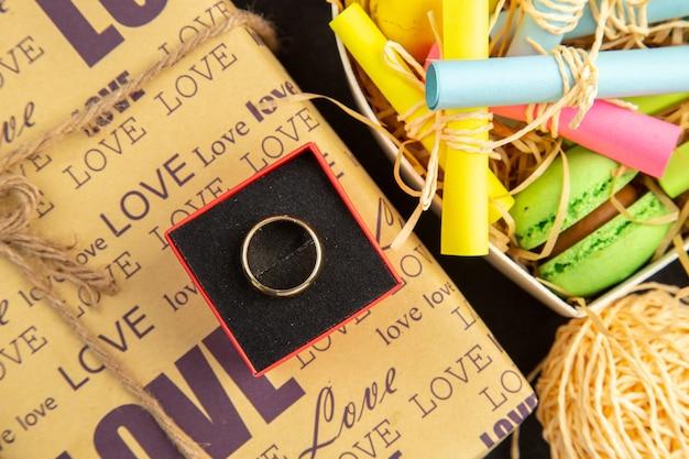 Vista dall'alto anello in scatola cuore scatola con foglietti adesivi arrotolati e macarons regali avvolti bouquet di fiori su sfondo scuro
