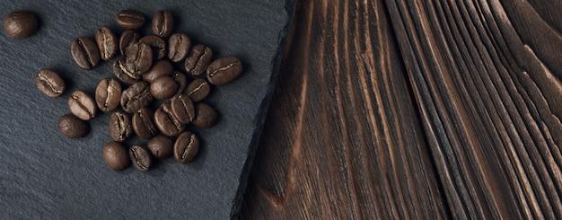 Vista superiore dei chicchi di caffè arrostiti sulla banda nera sulla tavola di legno marrone ruvida con lo spazio della copia