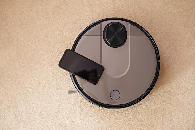 Vista dall'alto spazzatrice robotica per pavimenti, aspirapolvere robotico su tappeto con smartphone, casa intelligente
