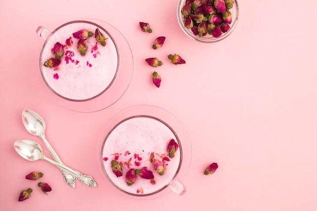 Vista dall'alto di rose moon latte in due tazze sul rosa
