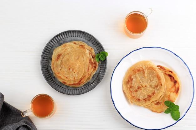 Vista dall'alto roti canai, cibo tradizionale a base di pane piatto popolare in indonesia durante la celebrazione di hari raya (ied fitr), solitamente servito con pollo al curry o manzo al curry. questo piatto viene dall'india