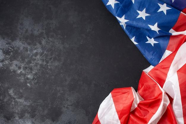 Bandiera degli stati uniti sgualcita vista dall'alto su sfondo nero con copia-spazio