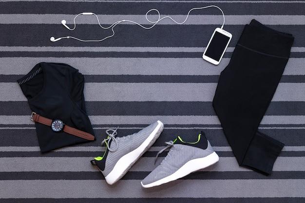 Vista dall'alto di scarpe da corsa, abbigliamento da donna, calzamaglia, applicazione per smartphone eseguita su tappeto grigio.