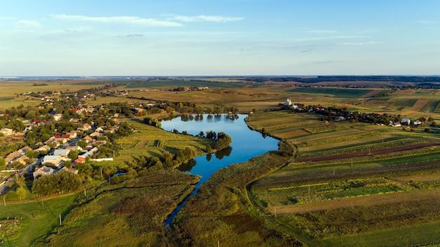 Vista dall'alto del paesaggio rurale in una giornata di sole primaverile. casa e campo verde. fotografia con drone