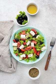 Vista dall'alto insalata con formaggio feta, erbe aromatiche e olive