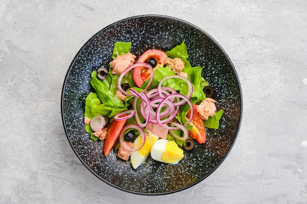 Vista dall'alto di insalata con lattuga, salmone, pomodoro, uova sode e cipolla con olive