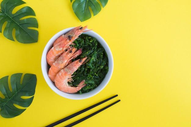Vista dall'alto di insalata con alghe e gamberi rossi nella ciotola bianca su sfondo giallo. avvicinamento.