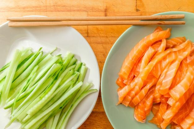 Vista dall'alto di fette di salmone e cetriolo fresco su piatti e bacchette di bambù