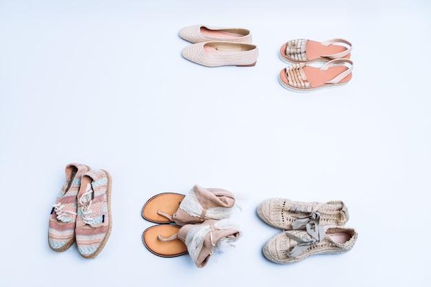 Vista dall'alto di sandali o scarpe estive su sfondo bianco. concetto di moda estiva