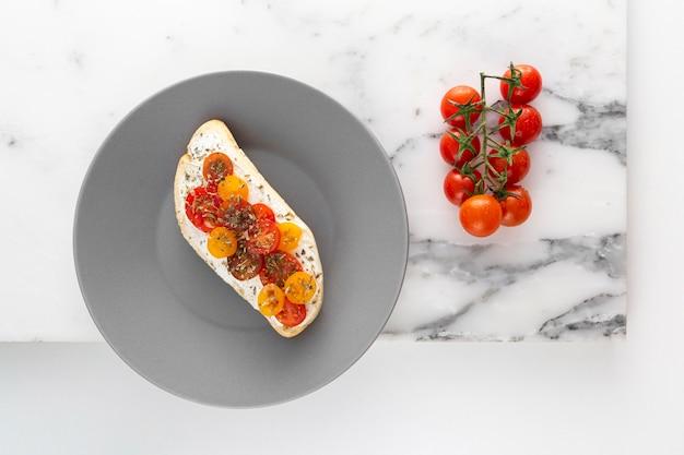 Vista dall'alto panino con crema di formaggio su piastra con pomodori