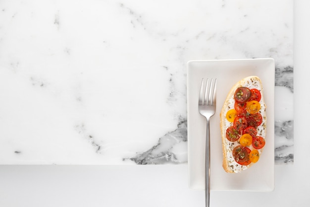 Vista dall'alto panino con crema di formaggio e pomodori sul piatto con forchetta e copia-spazio